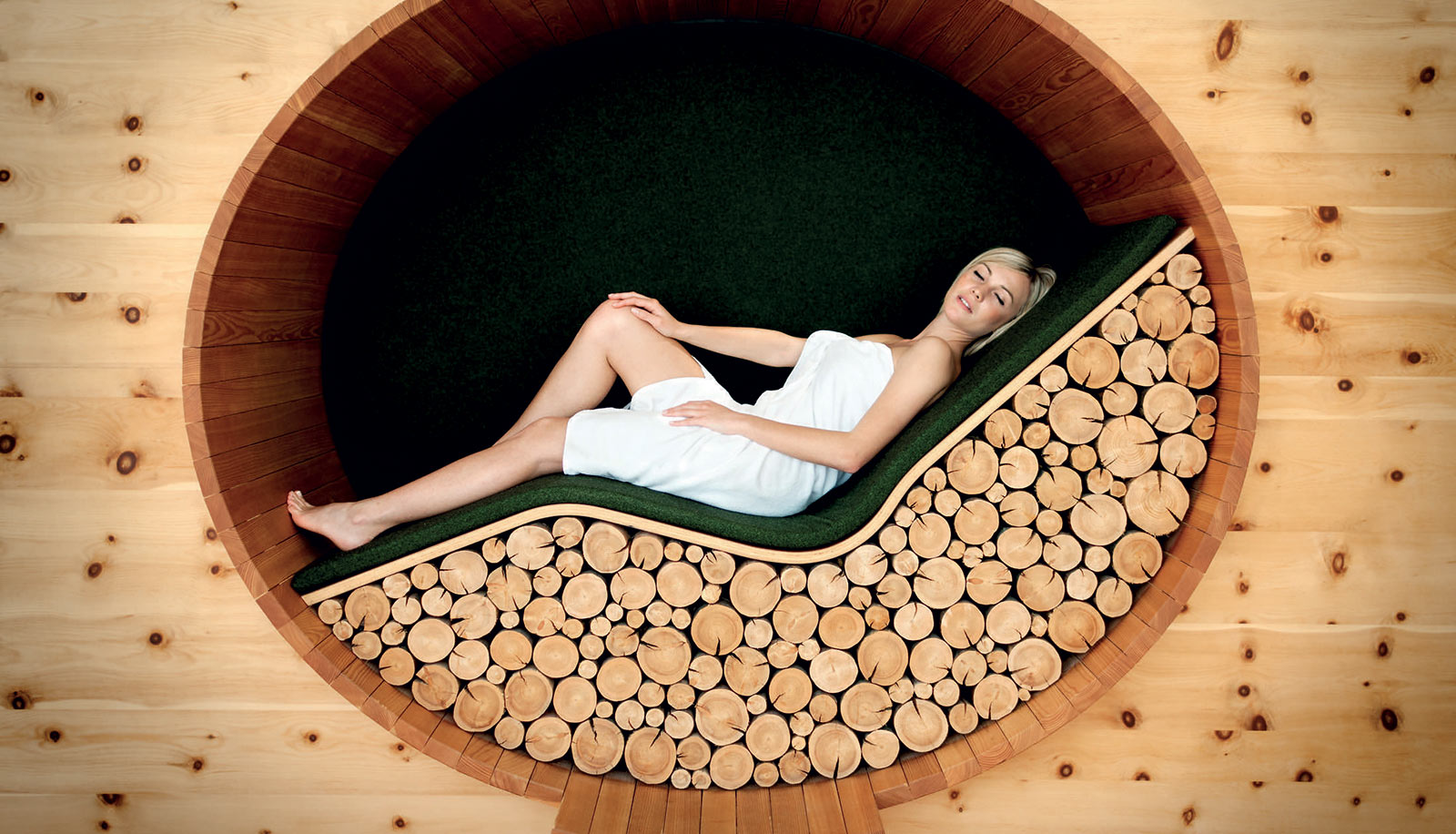 Young woman relaxing on a wooden lounge bed made of logs