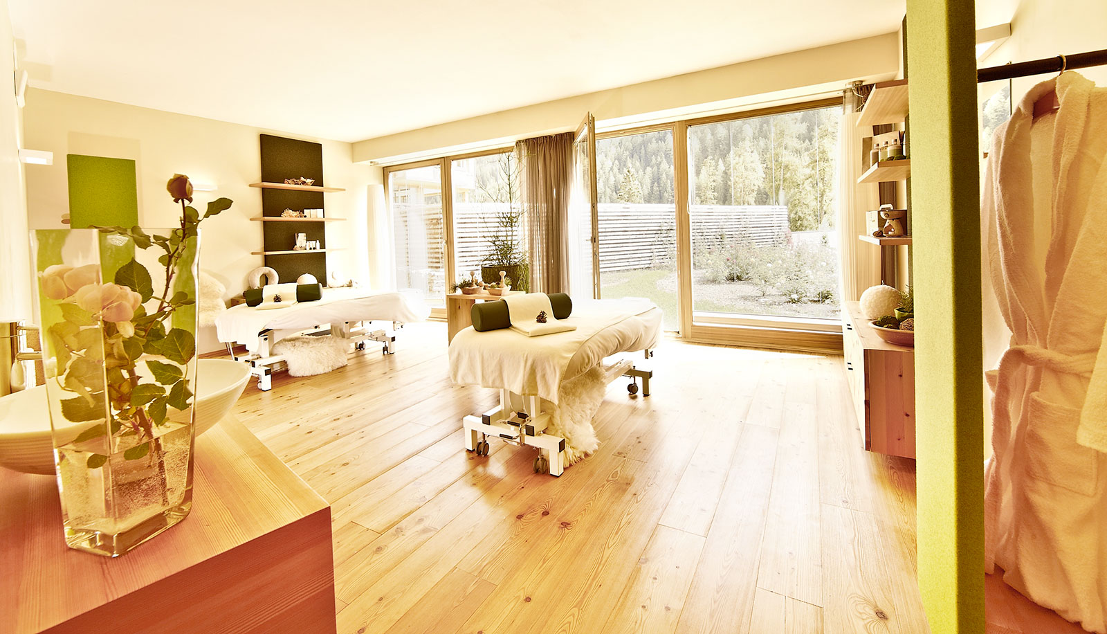 Treatment room of Arosea Hotel in Ultental-Val d'Ultimo with massage bed, wooden floor and view of the garden