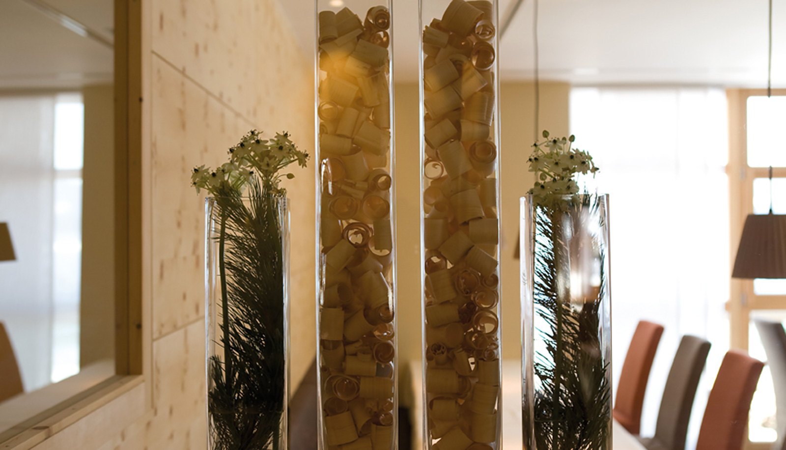 Decoration with woodchips and flowers in tall glass vases