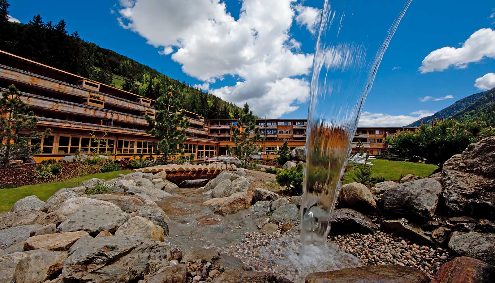 Exterior view of Arosea Hotel in Ultental-Val d'Ultimo as seen from a fountain