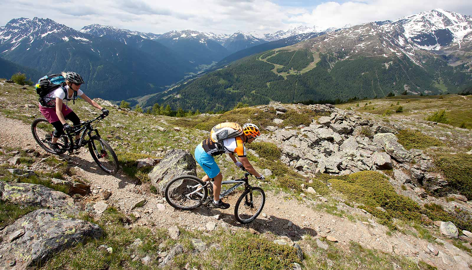 Two Mountain Bikers on a steep mountain path among the rocks with snowy mountains in the background