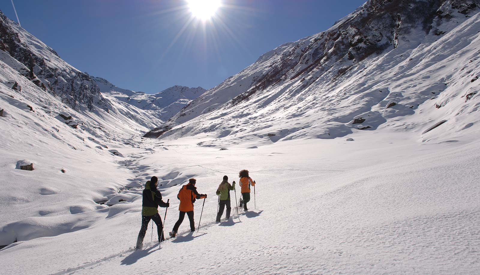 Four snow-shoe hiker on a snowy path on a sunny day