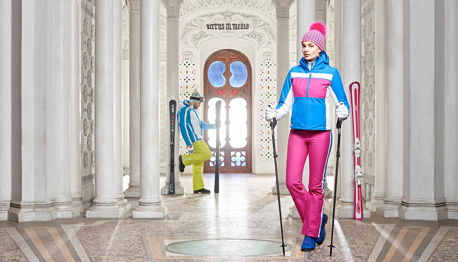 A man and a woman with skis in a Middle Eastern looking hall