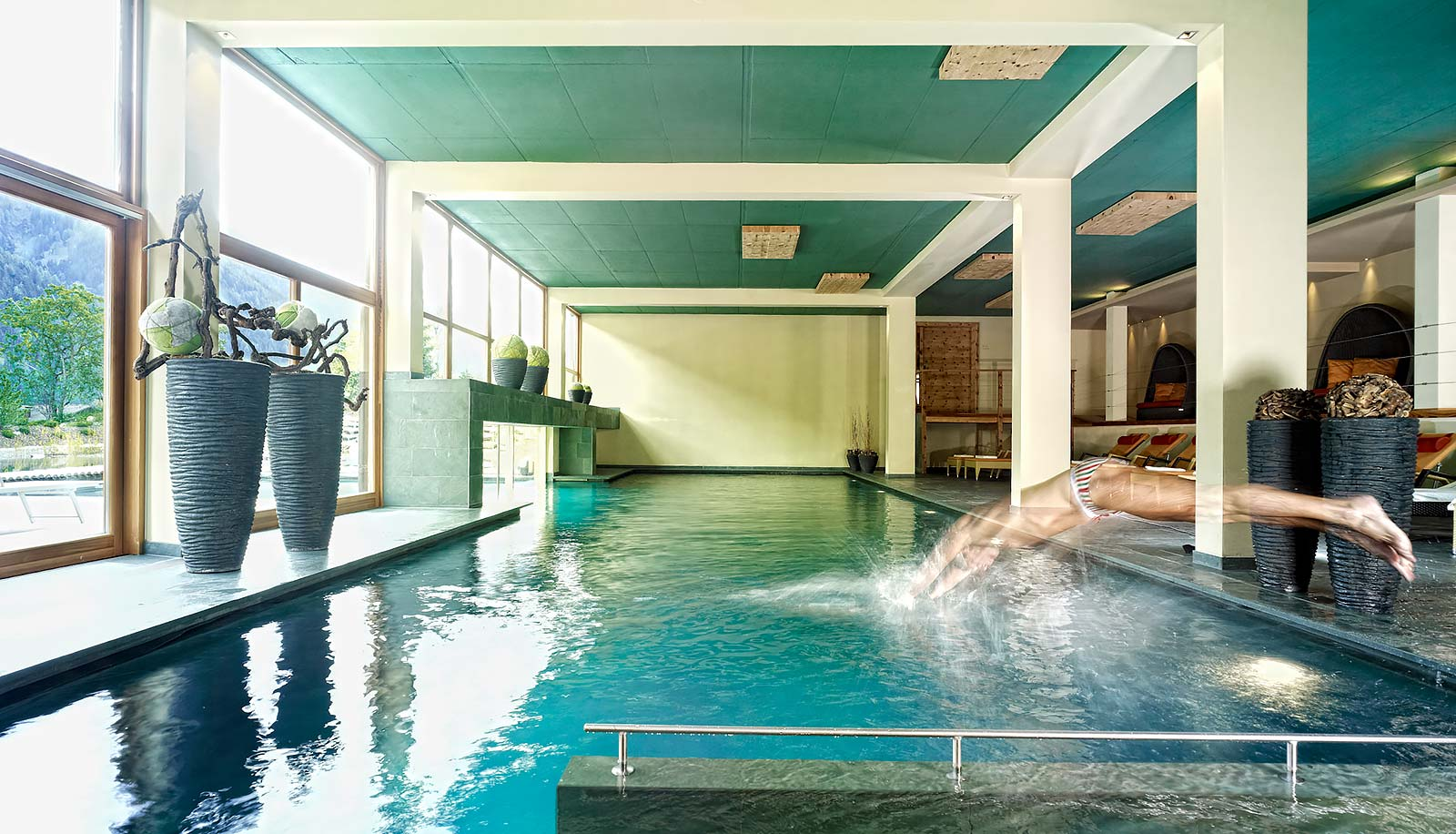 Swimmer jumping into the indoor pool at Arosea Life Balance Hotel in Ultental-Val d'Ultimo
