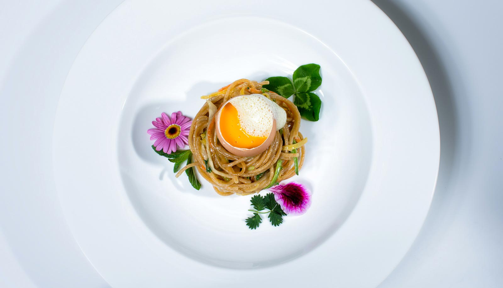 Spaghetti with vegetables and a whole egg, decorated with flowers